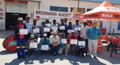 Fourteen brickmaking trainees receivin a certificate of attendance