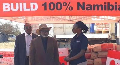 Ohorongo Cement's Esther Mbathera handing over the cement to the Founding Father Dr Sam Nujoma